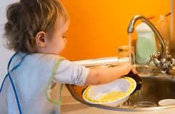 Baby boy washes plate Royalty Free Stock Images