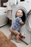 Baby boy with washing machine Stock Image