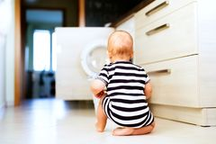 Baby boy by the washing mashine in the kitchen. Stock Image