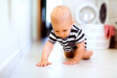Baby boy by the washing mashine in the kitchen. Stock Images