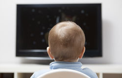 Baby boy watching cartoons on TV Stock Images