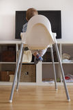 Baby boy watching cartoons on TV. He is sitting on his highchair. Back view stock photos