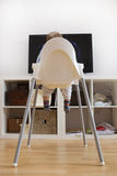 Baby boy watching cartoons on TV. He is sitting on his highchair. Back view royalty free stock photos
