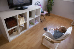 Baby boy watching television on his armchair Royalty Free Stock Image