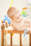 Baby boy. Waving hand and standing up in crib Royalty Free Stock Images