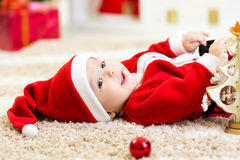 Baby boy weared Santa holding christmas ball. Happy Smiling baby lying on back wearing Christmas Santa hat and suit stock photo