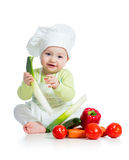Kid boy wearing chef. Baby boy wearing a chef hat with healthy food vegetables Royalty Free Stock Image