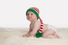 Baby Boy Wearing a Christmas Elf Stocking Cap. A seven month old baby boy crawling on a sheepskin rug. He is wearing a long, red, white and green striped Stock Image