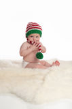 Baby Boy Wearing a Christmas Elf Stocking Cap. A seven month old baby boy sitting on a sheepskin rug. He is wearing a long, red, white and green striped stocking Royalty Free Stock Photography