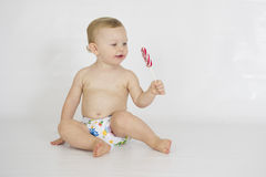 Baby boy wearing cloth reusable nappy. A baby boy eating a lollipop while wearing a printed cloth diaper of PUL Royalty Free Stock Photo