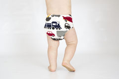 Baby boy wearing cloth reusable nappy. A baby boy walking while wearing a printed cloth diaper Stock Photo