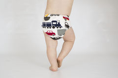 Baby boy wearing cloth reusable nappy. A baby boy walking while wearing a printed cloth diaper Royalty Free Stock Images