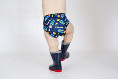 Baby boy wearing cloth reusable nappy. A baby boy walking while wearing a printed cloth diaper of PUL and wearing gumboots Royalty Free Stock Photo