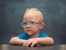 Baby boy wearing glasses with a clever look. In the background is black chalkboard Royalty Free Stock Photography