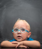 Baby boy wearing glasses with a clever look. In the background is black chalkboard Royalty Free Stock Image