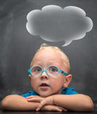 Baby boy wearing glasses with a clever look. In the background is black chalkboard Royalty Free Stock Photo