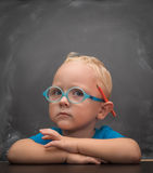 Baby boy wearing glasses with a clever look. In the background is black chalkboard Royalty Free Stock Photos