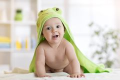 Baby boy wearing green towel in sunny bedroom. Newborn child relaxing after bath or shower.
