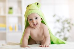 Baby boy wearing green towel in sunny bedroom. Newborn child relaxing after bath or shower. royalty free stock photo