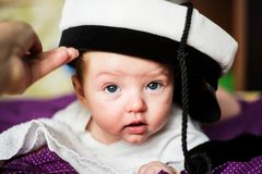 Baby boy wearing his fatheR`s student cap Stock Images