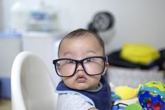 A baby boy is wearing a pair of eye glasses stock images