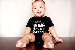 A baby boy is wearing a shirt with a message saying he is still living with my parents. A baby boy is wearing a black t-shirt with a message saying he is still stock photos