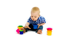 Baby boy on a white floor with toys Stock Images