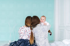 Baby boy in white pajamas looks over father`s shoulder while mother embraces him.  stock photography