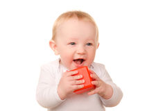 Baby boy in white playing with toy red block Stock Photos