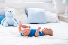 Baby boy in white sunny bedroom. Adorable baby boy in white sunny bedroom. Newborn child relaxing in bed. Nursery for young children. Textile and bedding for Stock Image