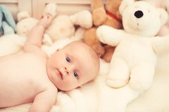 Baby boy and white teddy bear. Childhood and curiosity concept. Baby boy and his white teddy bear. Childhood and curiosity concept. Baby lying on white duvet stock photo