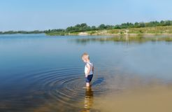 Baby boy in a white undershirt and shorts stand in river water. E view stock photo