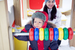 Baby boy on a winter playground Stock Photos