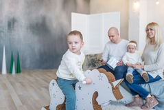 Baby boy on wooden horse swing. Parents with the little sister on background. royalty free stock photography
