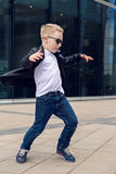 Baby boy 7 - 8 years in a black leather jacket dancing Royalty Free Stock Image
