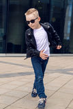 Baby boy 7 - 8 years in a black leather jacket dancing Royalty Free Stock Photography