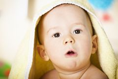 Baby boy with yellow blanket on head. Royalty Free Stock Photos