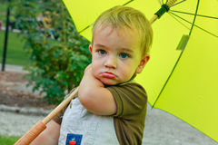 Baby boy with an yellow umbrella royalty free stock photos
