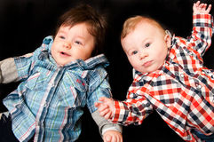 Baby boys on black. Two cute baby boys on black background Royalty Free Stock Images