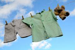 baby boys clothes and a teddy bear on a clotheline Royalty Free Stock Photo
