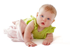 Baby with bright blue eyes cuddles soft blanket. Royalty Free Stock Photo