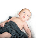Baby with bright blue eyes looking up with a suprised look on hi Royalty Free Stock Image