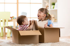 Baby brother and child sister playing in cardboard boxes. In nursery Royalty Free Stock Image