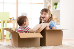 Baby brother and child sister playing in cardboard boxes Stock Photos