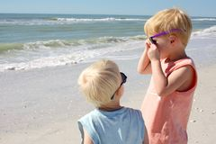 Baby Brother Looking at Older Child on Beach Stock Photos
