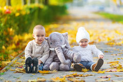Baby brother and sister having fun in fall park. Stock Image