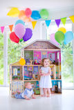 Baby brother and sister playing with a doll house. Adorable curly toddler girl in a white dress and her little baby brother playing together with a birthday royalty free stock photo