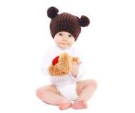 Baby in bruine hoedenzitting met stuk speelgoed Royalty-vrije Stock Afbeelding