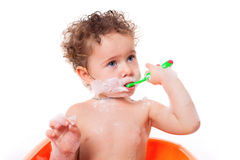 Baby brushing teeth in bath Stock Images
