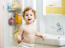Baby brushing teeth in bathroom Royalty Free Stock Photo